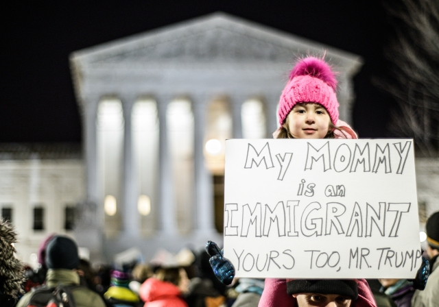 immigration sign held by child